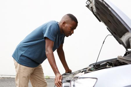 Zij portret van jonge Afrikaanse man op zoek onder de motorkap van de auto