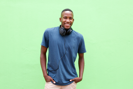 man shirt: Portrait of handsome young  man smiling with headphones against green background
