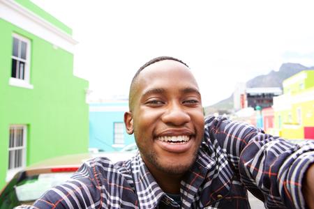 Feche acima do homem novo feliz na rua da cidade tomando um auto-retrato Imagens
