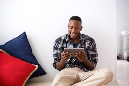 black male: Portrait of happy young african man sitting on floor and using digital tablet at home Stock Photo