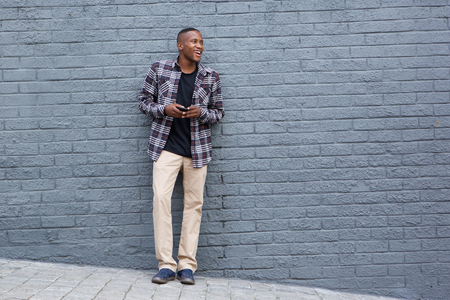 leaning: Full length portrait of stylish young african man holding a mobile phone and looking away at copy space