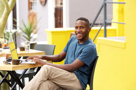 black guy: Portrait of smiling young black guy sitting at a cafe with a laptop