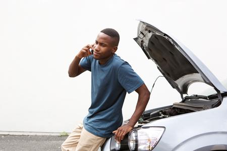 Portret van een jonge Afrikaanse man mobiel bellen op voor auto service