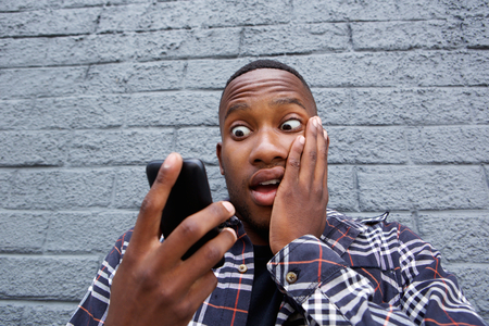 black guy: Close up portrait of young african man reading bad message on his mobile phone. Stock Photo