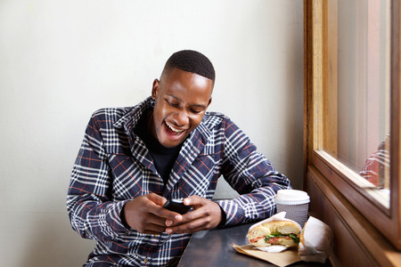 Portrait of smiling young african man sitting at a cafe and reading text message on his cell phone