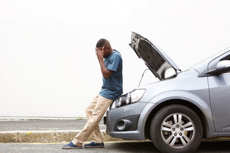 man machine: Full length portrait of upset young african man standing in front of a broken down car parked on the side of a road Stock Photo