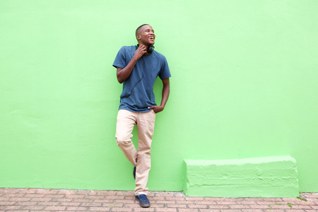 african american man: Full length portrait of stylish young african man standing against a green wall and looking away