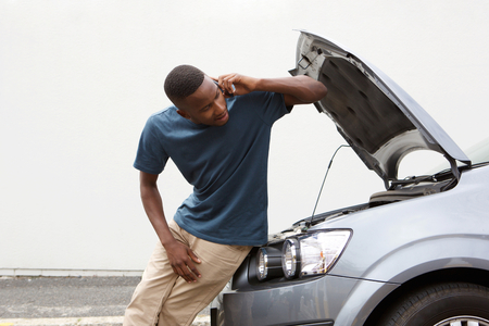 calling for help: Portrait of young african guy standing near broken car and calling for help on mobile phone
