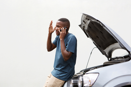 Portrait of young african man calling technical car service while standing by his breakdown car outdoors