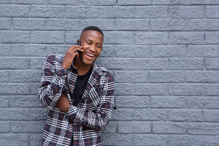afro man: Portrait of a happy african man using mobile phone and smiling against gray wall