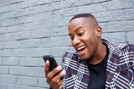 riendo: Cerca retrato de hombre joven afroamericana de leer un mensaje de texto divertido en su teléfono móvil y se ríe Foto de archivo