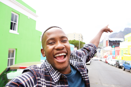 Close up of excited young african guy out on the city street taking a self portrait