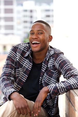 persona sentada: Retrato de hombre joven africana sonriente sentado en un banco al aire libre