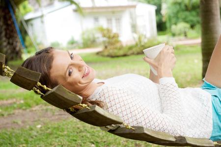 hammock: Side portrait of a beautiful woman relaxing on hammock with coffee cup Foto de archivo