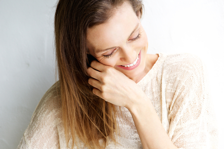 middle adult: Close up candid portrait of a woman laughing against white background