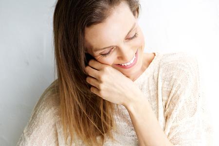 Close-up candid portret van een vrouw lachend tegen een witte achtergrond Stockfoto