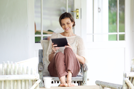 human face: Portrait of a smiling woman sitting with digital tablet