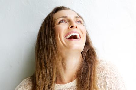 Close up Porträt einer schönen Frau mittleren Alters lachend vor weißem Hintergrund Lizenzfreie Bilder