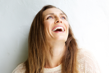 Zblízka portrét krásné středního věku ženy se smíchem proti bílému pozadí Reklamní fotografie