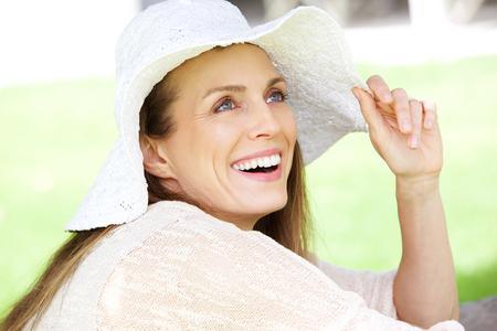 모자와 함께 웃고있는 자연 여자의 초상화를 닫습니다