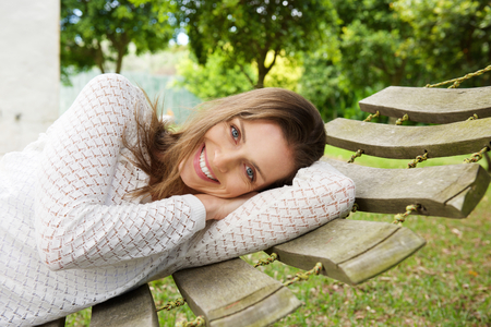one woman: Close up portrait of a smiling attractive woman relaxing on hammock outside