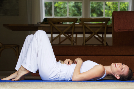 woman laying: Side portrait of a yoga woman laughing on floor a home Stock Photo