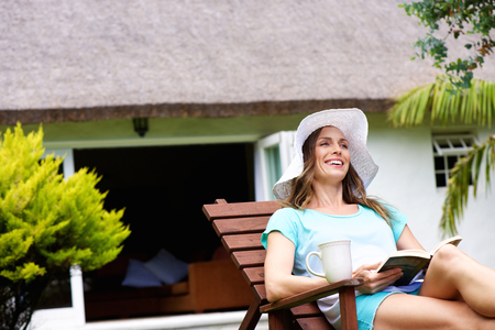 rest in peace: Portrait of a happy woman sitting outside with book