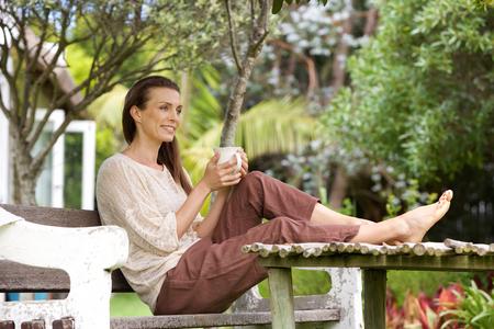 Portret van een oudere vrouw buiten zitten met een kopje koffie Stockfoto