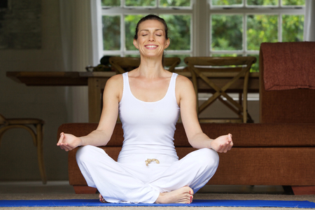 meditation room: Older woman sitting on floor in yoga position at home