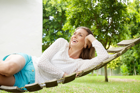 woman laying: Portrait of a beautiful woman smiling on hammock outdoors Stock Photo