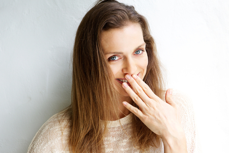covering: Candid portrait of a smiling woman with hand covering mouth