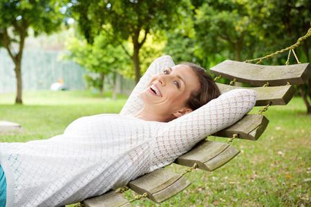 Portret van een lachende oudere vrouw ontspannen op hangmat buitenshuis