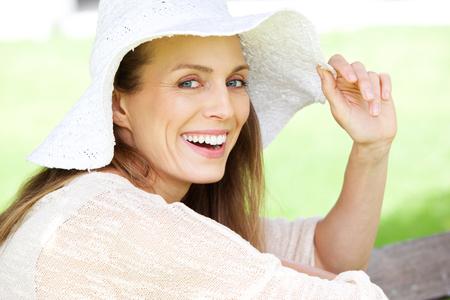 태양 모자와 함께 웃 고 아름 다운 여자의 초상화를 닫습니다