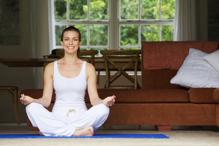 Attractive woman sitting on floor at home in yoga position Standard-Bild
