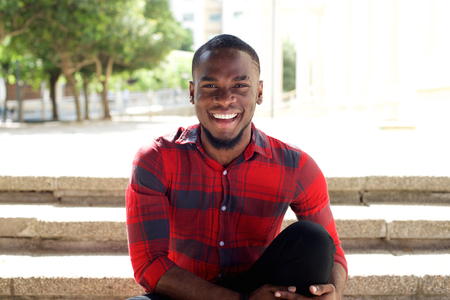 Close up portrait of smiling young african man sitting outdoors on steps Archivio Fotografico