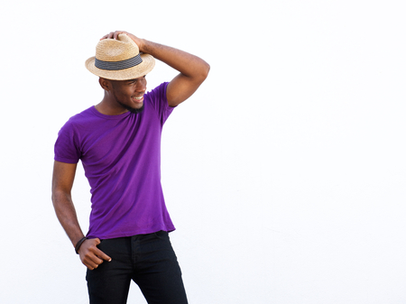 Portrait of a stylish young african guy with hat looking away at copy space against white background