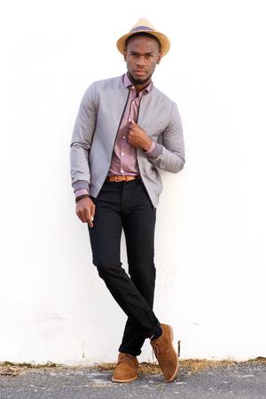 hombre con sombrero: Retrato de cuerpo entero de un hombre africano joven de pie contra el fondo blanco
