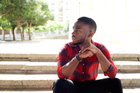 Close up portrait of pensive young african man sitting outdoors on steps and looking away