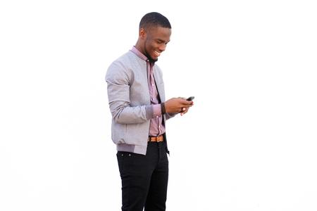 Portrait eines glücklichen jungen afrikanischen Mann liest SMS auf Handy vor weißem Hintergrund