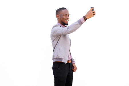 black male: Portrait of an attractive young man talking a selfie with mobile phone against white background