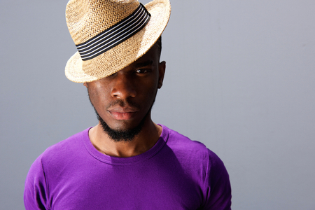 suave: Close up portrait of cool young fashion model with hat against gray background Stock Photo