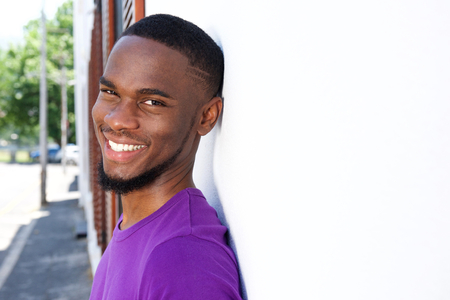 Close up portrait of a cheerful young african american leaning to a wall outdoors Stock Photo