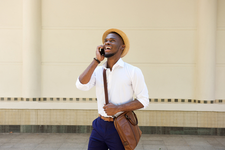 sidewalk talk: Portrait of a happy young african guy standing on sidewalk with cellphone