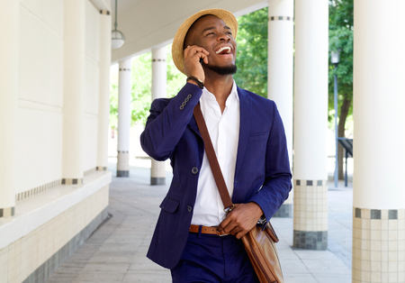 black guy: Portrait of a smiling black guy walking and talking on mobile phone