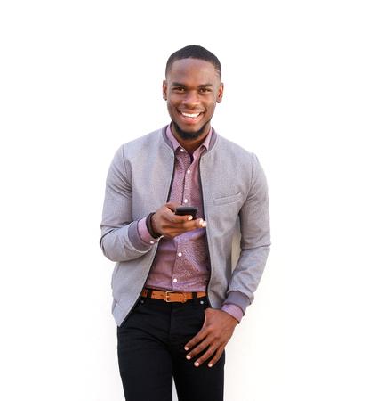白い背景に、携帯電話の側に立って、ハンサムな若いアフリカ男の肖像