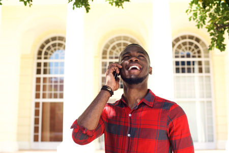 african man: Portrait of a young african man talking on mobile phone and smiling