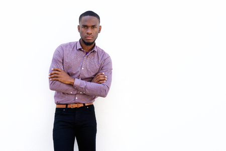 casual business man: Portrait of young african man with his arms crossed while standing against white background