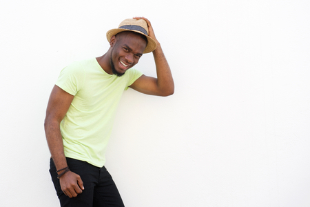 Portrait of a young black man smiling with hat standing against white background