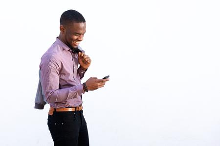 Portrait d'un jeune africain gars lecture message texte sur un téléphone cellulaire sur le fond blanc