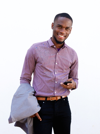 phone isolated: Portrait of a handsome young man standing with a mobile phone against white background Stock Photo